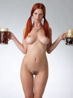 Sexy Redhead Babe Holding Beer Mugs - sultry centerfold with big natural booby